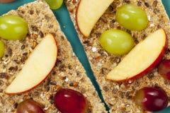 Segmentos e uvas de Apple no pão estaladiço do multigrain Imagem de Stock Royalty Free