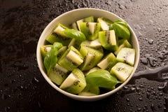 Segments découpés en tranches de kiwis avec des feuilles de basilic Image stock
