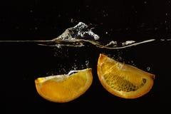 Segments of fresh orange falling into the water Royalty Free Stock Photos