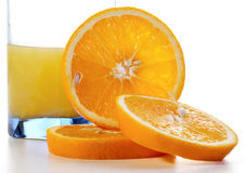 Segments of an orange and a glass of juice Stock Photography