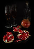 Segments of pomegranate and the whole fruit on a black background. With glasses royalty free stock photos