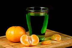 Segments of tangerine and glass with drink Royalty Free Stock Images
