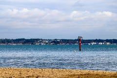 Segnale autoalimentato solare nel mare con la città sull'orizzonte immagini stock libere da diritti