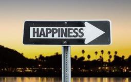 Segnale di direzione di felicità con il fondo di tramonto Fotografie Stock