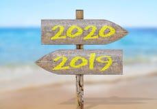 Segnale di direzione di legno con 2019 e 2020 Immagine Stock