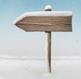 Segnale di direzione di legno con meno neve con le precipitazioni nevose su fondo Fotografia Stock