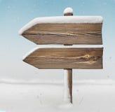 Segnale di direzione di legno con meno neve e precipitazioni nevose BG two_arrows Fotografie Stock