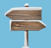 Segnale di direzione di legno con meno neve sul blu two_arrows-opposit Fotografia Stock