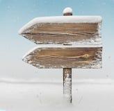 Segnale di direzione di legno con neve e le precipitazioni nevose BG two_arrows-one_ Immagine Stock