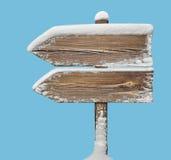 Segnale di direzione di legno con neve sul blu two_arrows-one_directio Fotografie Stock