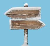 Segnale di direzione di legno con neve sul blu two_arrows-opposite_dir Immagini Stock Libere da Diritti