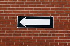 Segnale di direzione su un muro di mattoni Fotografie Stock Libere da Diritti