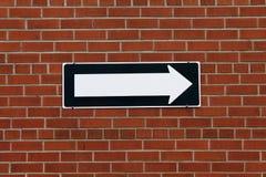 Segnale di direzione su un muro di mattoni Fotografia Stock Libera da Diritti