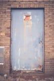 Segnale di pericolo ad alta tensione arrugginito ad una vecchia porta del metallo Immagini Stock Libere da Diritti