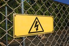 Segnale di pericolo ad alta tensione sulla rete del recinto di filo metallico Fotografie Stock Libere da Diritti