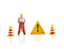 Segnale di pericolo in costruzione con la figura miniatura labo Fotografie Stock Libere da Diritti
