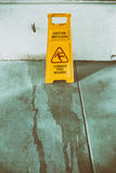 Segnale di pericolo della superficie sdrucciolevole del pavimento e simbolo in costruzione, corridoio Fotografia Stock