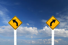 Segnale di pericolo di giro destro e sinistro con cielo blu fotografie stock