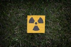 Segnale di pericolo di radiazione su un'erba verde Immagine Stock Libera da Diritti