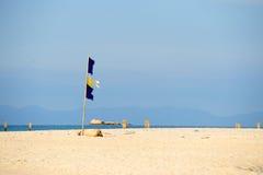 segnale di pericolo di un danno della bandiera ad una bella spiaggia con una s blu Fotografia Stock Libera da Diritti