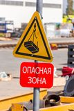 segnale di pericolo di un calo possibile in carico da una gru su un fondo giallo immagine stock libera da diritti