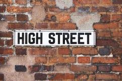 Segnale stradale arrugginito del via principale del metallo sul muro di mattoni Fotografie Stock