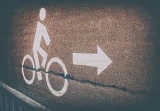 Segnale stradale bianco della bicicletta sul vicolo dell'asfalto con il simbolo della freccia nel vin Fotografia Stock