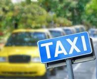 Segnale stradale blu del taxi nella parte anteriore una fila delle automobili del taxi Fotografie Stock Libere da Diritti