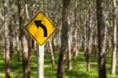 Segnale stradale che mostra una curvatura nella strada davanti all'albero di gomma p Immagine Stock
