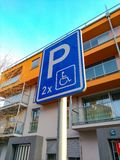 Segnale stradale che parcheggia per la gente con le inabilità sui precedenti di bella casa fotografia stock