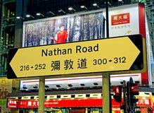 Segnale stradale con la pubblicità dietro su Nathan Road in Tsim Sha Tsui, Hong Kong Immagine Stock Libera da Diritti