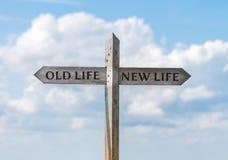 Segnale stradale con vecchia vita e nuova direzione di vita contro il cielo Immagini Stock