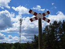 Segnale stradale d'avvertimento dell'incrocio di ferrovia con la foresta e torre di radiodiffusione a fondo immagine stock