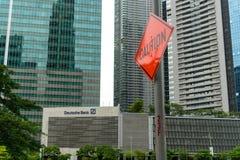 """segnale stradale del  del """"Caution†accanto al logo di Deutsche Bank fotografie stock"""