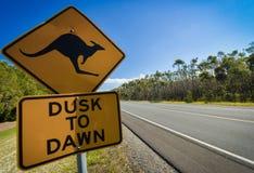 Segnale stradale del canguro accanto ad una strada principale, Australia fotografia stock libera da diritti