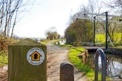 Segnale stradale dell'argine del ` s di Offa e ponte di ascensore su Montgomery Canal, Powys, Galles fotografia stock libera da diritti
