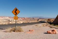 Segnale stradale della curva con le montagne rosse cremose della roccia in valle di fuoco Fotografia Stock Libera da Diritti