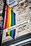 Segnale stradale di Sainte Catherine e una bandiera di gay pride dell'arcobaleno fotografia stock libera da diritti
