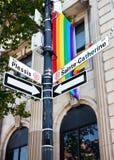 Segnale stradale di Sainte Catherine e una bandiera di gay pride dell'arcobaleno fotografie stock