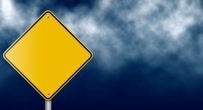 Segnale stradale giallo in bianco sul cielo tempestoso fotografia stock