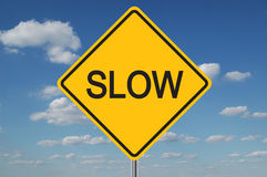 Segnale stradale lento con le nubi Immagine Stock Libera da Diritti