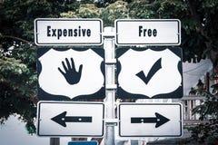 Segnale stradale libero contro costoso immagini stock libere da diritti
