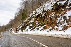 Segnale stradale limite di velocità sulla strada della montagna di inverno Immagini Stock Libere da Diritti