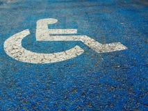 Segnale stradale per la gente con le inabilità su fondo blu immagine stock