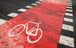 Segnaletica stradale rossa della bicicletta sulla strada urbana fotografie stock libere da diritti