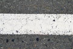 Segnaletiche stradali bianche della banda sulla strada asfaltata fotografia stock libera da diritti