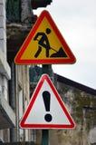 Segnali stradali con un punto esclamativo e un uomo che scavano la terra I lavori stradali sono in corso Fotografie Stock