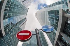 Segnali stradali sui precedenti degli edifici per uffici. immagine stock