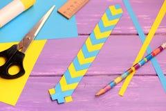 Segnalibro di carta blu e giallo su un fondo di legno lilla Segnalibro semplice con progettazione di carta Cancelleria messa su u Immagini Stock Libere da Diritti