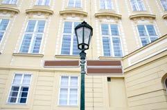 Segni e iluminazione pubblica direzionali in bianco con costruzione nei precedenti Fotografia Stock